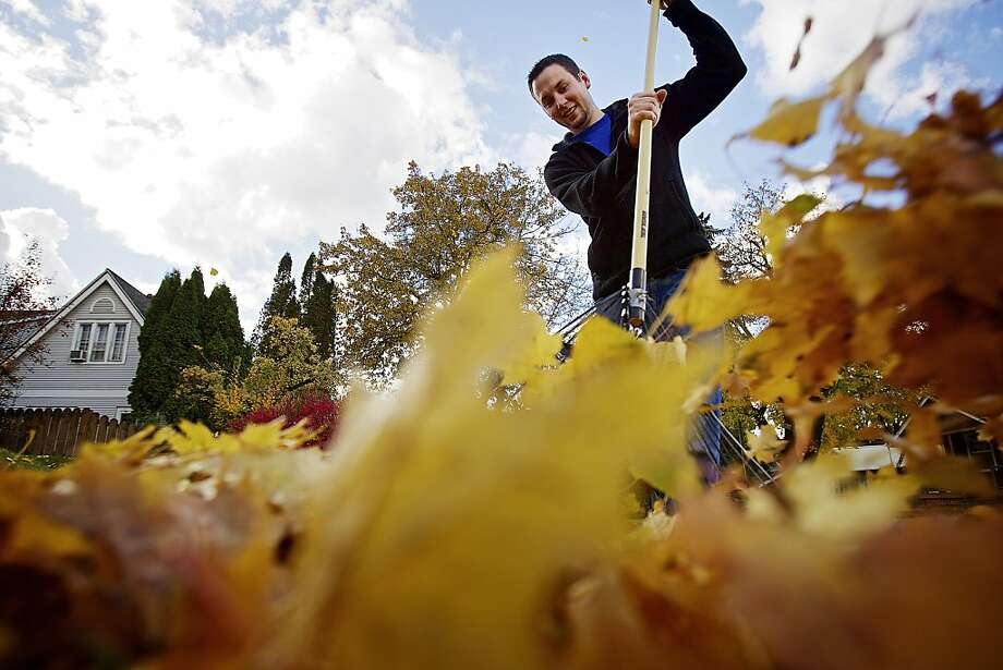 No more wide-angle shots! Jason Droesch tries to rake a photographer off his lawn in Coeur d'Alene, Idaho. Photo: Jerome A Pollos, Associated Press
