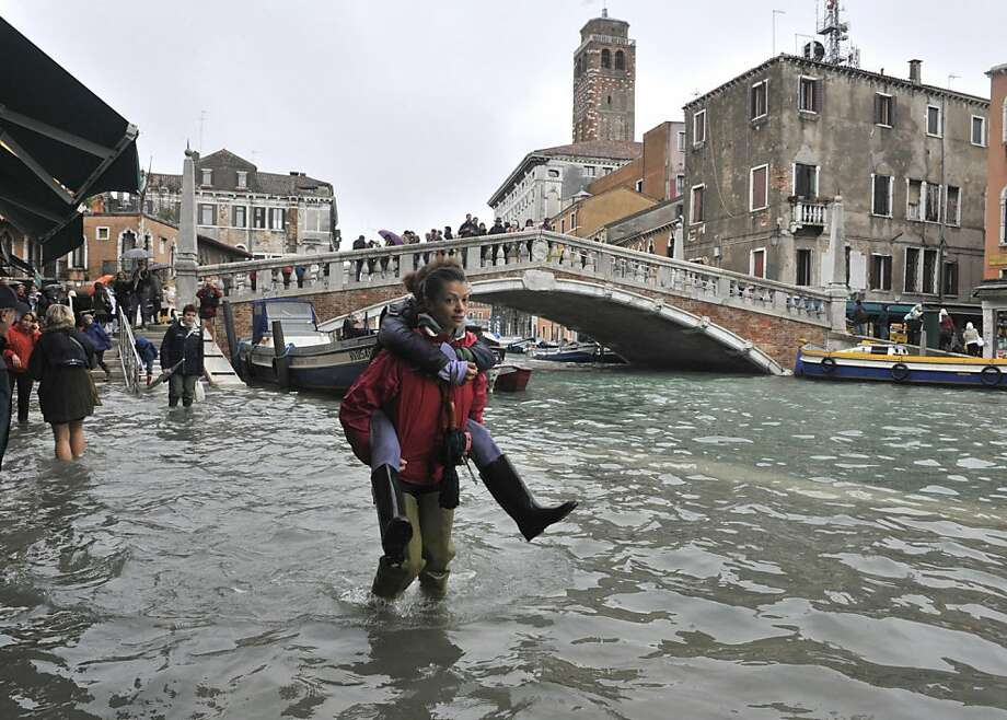 No reason both us should get our feet wet: A pedestrian catches a piggyback ride near the Ponte delle Guglie in Venice. High tides often flood Venice this time of year, leading Venetians and tourists to don high boots and use wooden walkways to cross St. Mark's Square and other areas. Photo: Luigi Costantini, Associated Press