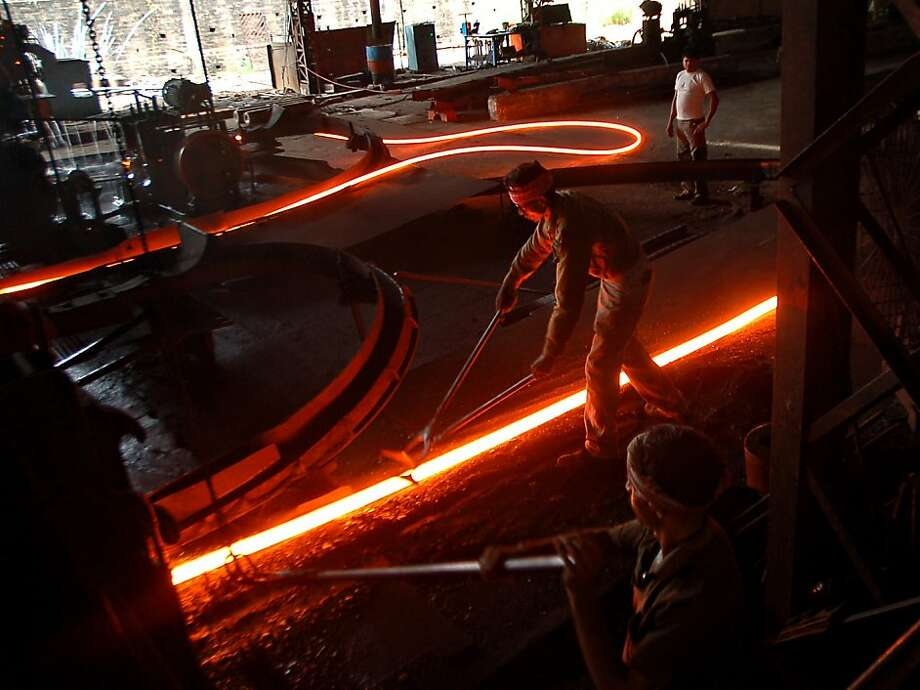 Glowing like lasers, lengths of red-hot metal are shaped at a steel factory on the outskirts of Agartala, India. Photo: Strdel, AFP/Getty Images
