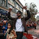 Angel Pagan raises both fists in the air as he rides in a car with his family during the San Francisco Giants World Series victory parade on Wednesday, October 31, 2012 in San Francisco, Calif.