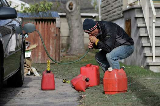 Chris Zaturoski uses a garden hose to attempt to siphon gasoline from his car to use in a generator at his house which is without power in the wake of superstorm Sandy on Thursday, Nov. 1, 2012, in Little Ferry, N.J. The hose was too big to fit into the gas tank of the car.  New Jersey residents across the state were urged to conserve water. At least 1.7 million customers remained without electricity. Photo: Mike Groll, Associated Press / AP