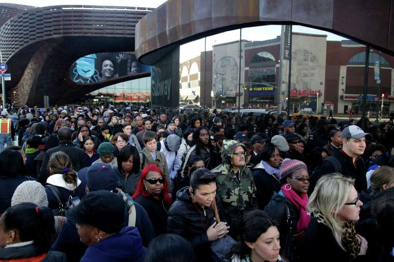Commuters wait in a line to board buses into Manhattan in front of the Barclays Center in Brooklyn,