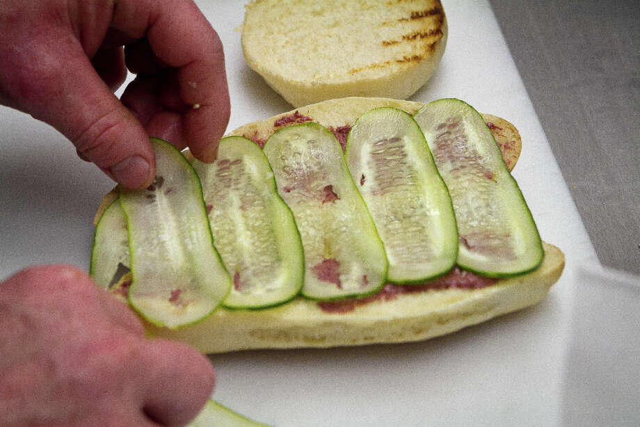 Pickles being added to the Bahn Mi sandwich at Pig and Pie. Photo: John Storey, Special To The Chronicle / ONLINE_Yes