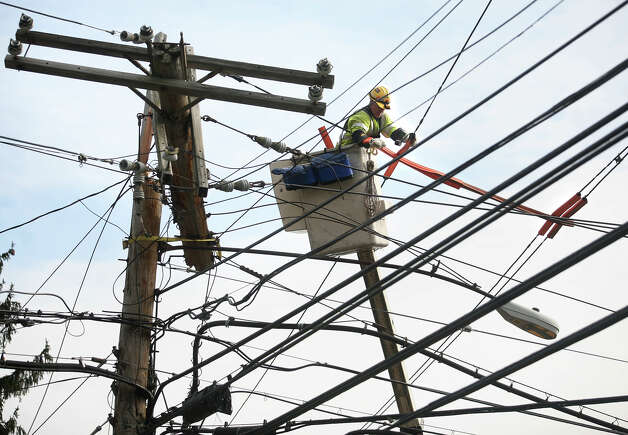 A United Illuminating worker insulates crossed wires while working to restore power to Black Rock Turnpike businesses at the intersection of the Black Rock Turnpike and Burroughs Road in Fairfield on Thursday, November 1, 2012. Photo: Brian A. Pounds / Connecticut Post