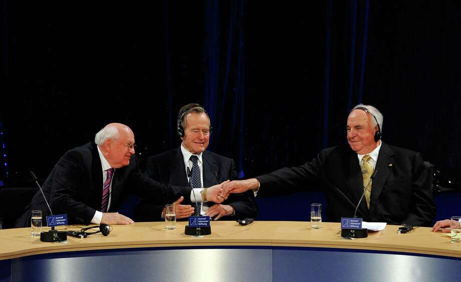 The former Soviet President Mikhail Gorbachev, left, shakes hands with former German Chancellor Helmut Kohl while former U.S. President George H. W. Bush sits between them at Friedrichstadtpalast on Oct. 31, 2009 in Berlin, Germany. Photo: Steffen Kugler, Getty Images / Getty Images Europe
