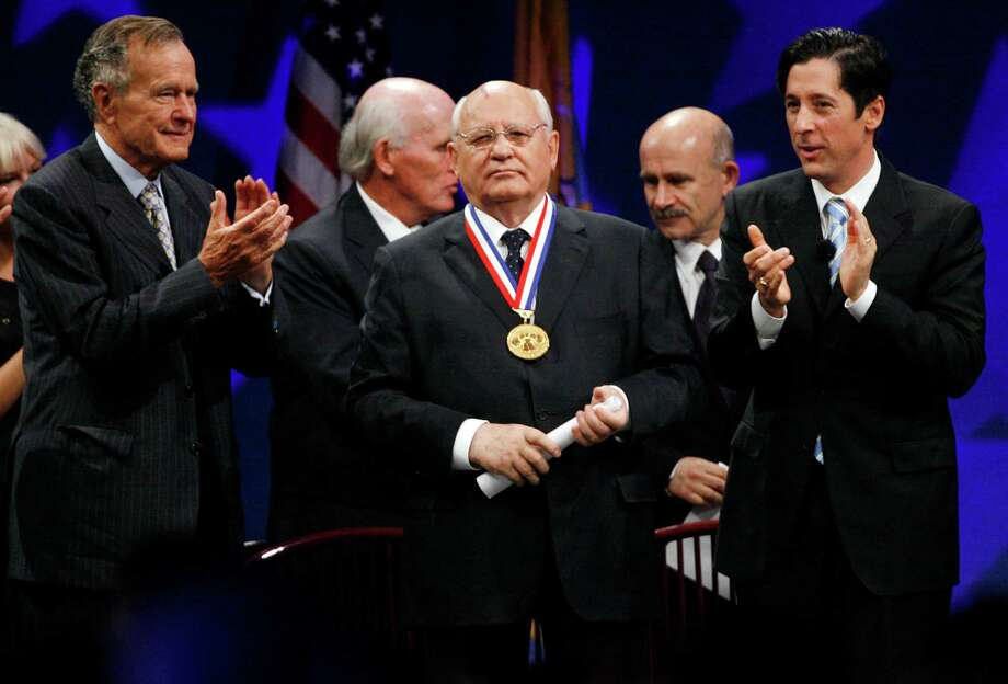Mikhail Gorbachev, center, the former Soviet leader and 2008 Liberty Medal winner, is applauded by former U.S. President George H.W. Bush, left, Chairman of the National Constitution Center, and Joseph Torsella, right, president of the center, following Gorbachev's remarks, Thursday, Sept. 18, 2008, in Philadelphia. Gorbachev is being honored for his role in ending the Cold War. Photo: Tom Mihalek, AP / AP