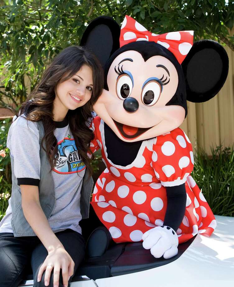 "In this image released by Disney, singer and actress Selena Gomez, star of the Disney Channel series ""Wizards of Waverly Place"", poses with Minnie Mouse, Wednesday, April 30, 2008 at Disney's Hollywood Studios in Lake Buena Vista, Fla.  Gomez is at Walt Disney World this week to take part in the ""Disney Channel Games,"" a made-for-television, Olympic-style competition that will air this summer on the Disney Channel. Photo: Matt Stroshane, AP / DISNEY"