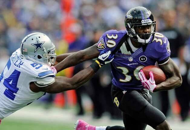 Baltimore Ravens running back Bernard Pierce, right, tries to outrun Dallas Cowboys inside linebacker Bruce Carter in the first half of an NFL football game in Baltimore, Sunday, Oct. 14, 2012. (AP Photo/Nick Wass) Photo: Nick Wass, Associated Press / FR67404 AP
