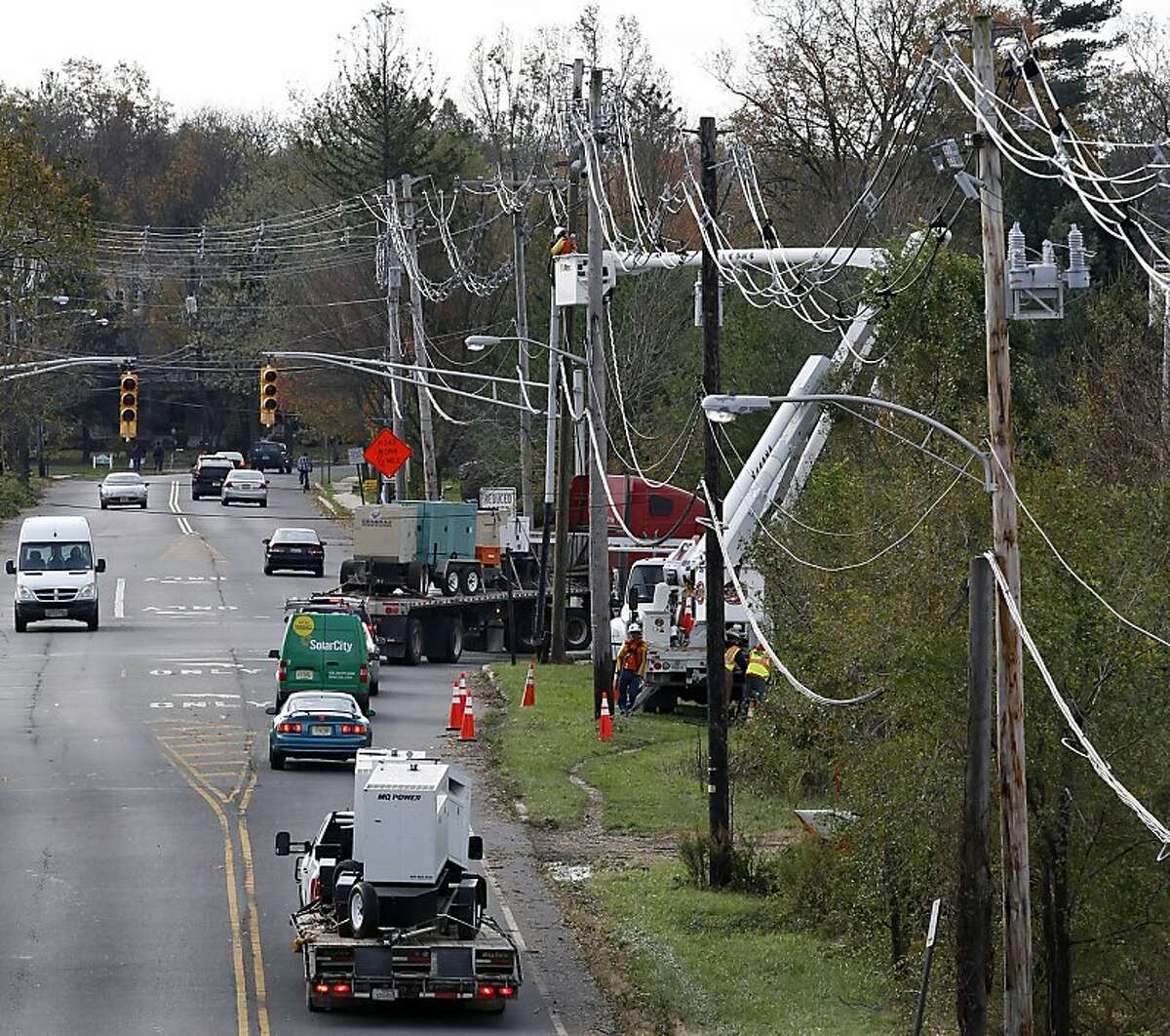 Trucks carry portable generators as crews work on power lines damaged by the superstorm in Hightstown, N.J.