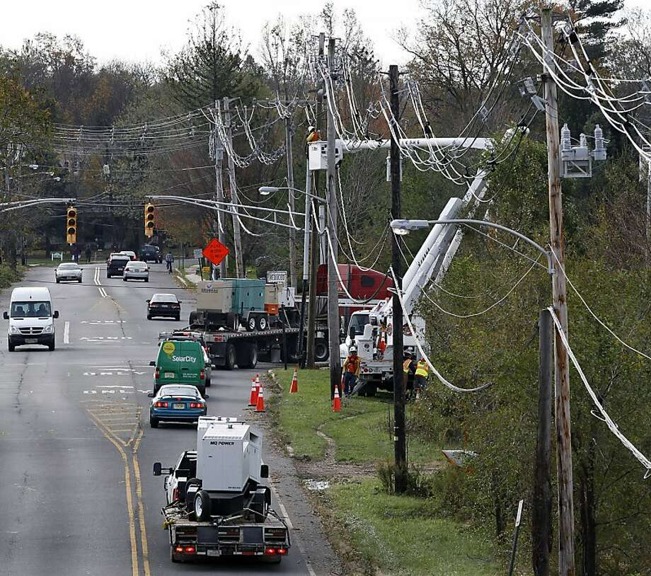 Trucks carry portable generators as crews work on power lines damaged by the superstorm in Hightstown, N.J. Photo: Mel Evans, Associated Press