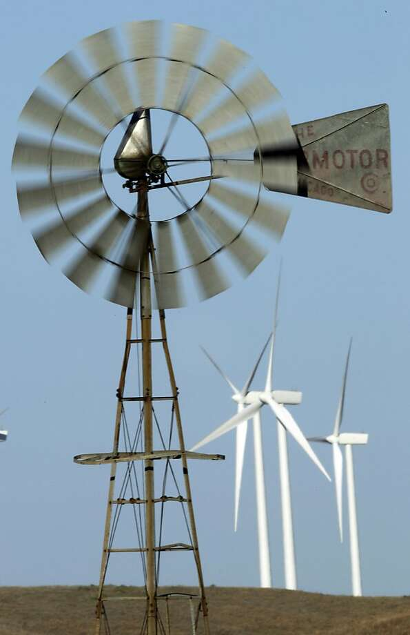 FILE - In this Oct. 20, 2010 photo, a working wind mill turns with a background of wind turbines from the Smoky Hills Wind Farm near Ellsworth, Kan. President Obama wants America to get 80 percent of its electricity from clean energy sources by 2035. Yetinvestors backing that ambitious goal have been punished lately. Photo: Orlin Wagner, AP