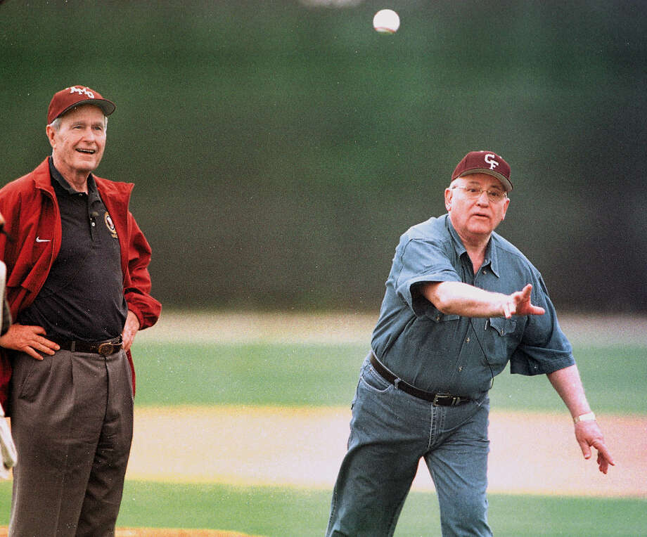 Former Soviet leader Mikhail Gorbachev throws out the first pitch as former President George H.W. Bush looks on before the start of a high school baseball game between A&M Consolidated High School and Cy-Fair High School, Thursday, April 12, 2001, in College Station. Gorbachev was in town to receive the inaugural Bush Award for Excellence in Public Service from the former president. Photo: BUTCH IRELAND, AP / BCS EAGLE