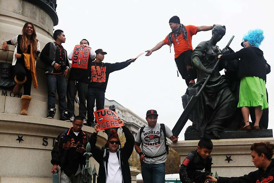 Vince Ferrer (orange shirt) grabs a poster as he tries to catch a glimpse of the stage in front of City Hall during a parade honoring the San Francisco Giants' victory in the World Series on October 31, 2012 in San Francisco, Calif. Photo: Pete Kiehart, The Chronicle