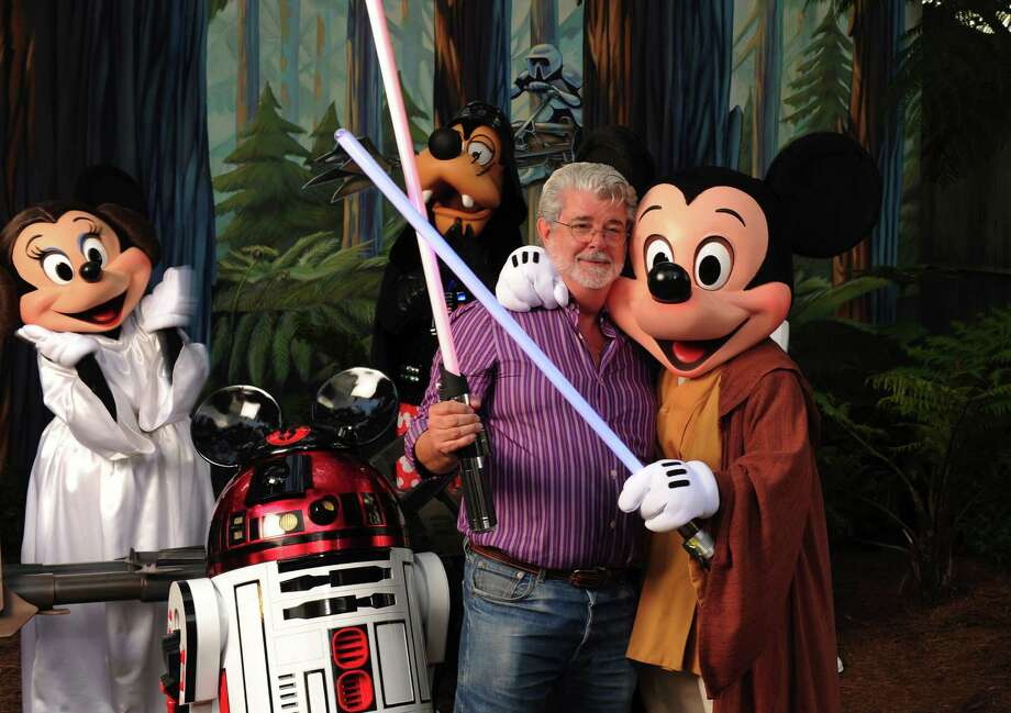 """FILE - OCTOBER 30:  It was reported October 30, 2012 that The Walt Disney Company will buy Lucasfilm Ltd. for USD 4.05 billion and begin plans for Star Wars: Episode VII  LAKE BUENA VISTA, FL - AUGUST 14:  In this handout image provided by Disney, """"Star Wars"""" creator and filmmaker George Lucas meets a group of """"Star Wars""""-inspired Disney characters Aug. 14, 2010 at Disney's Hollywood Studios theme park in Lake Buena Vista, Fla.  Lucas is in central Florida for """"Star Wars Celebration V,"""" the official Lucasfilm fan event that is taking place this week at the Orange County Convention Center in Orlando, Fla. (Photo by Todd Anderson/Disney via Getty Images) Photo: Handout / 2010 Disney"""