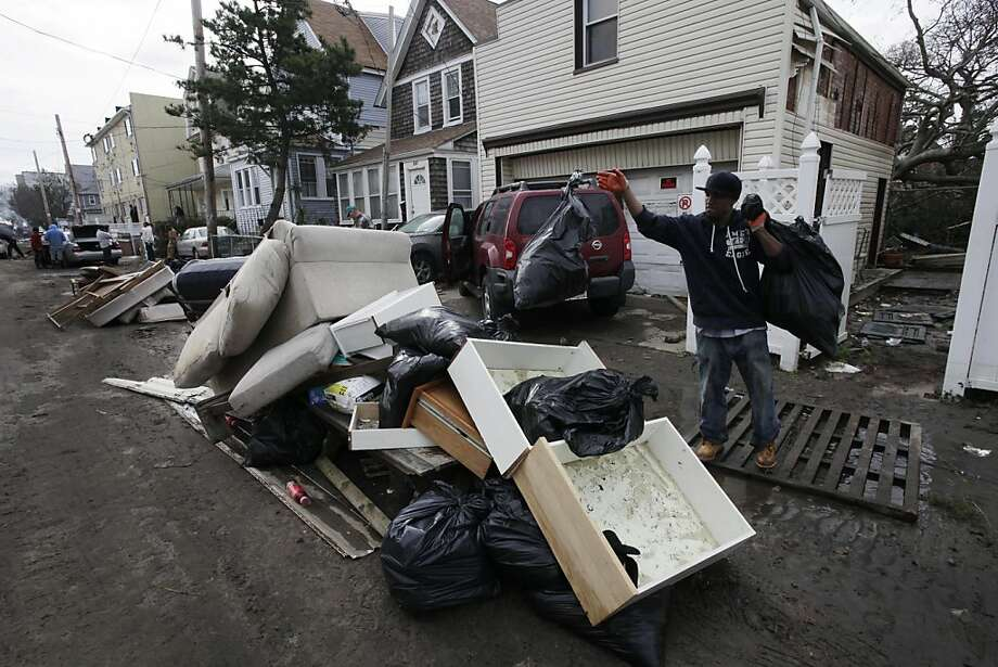 Carlos Arias removes bags of storm-damaged items from his home and piles them in the street in Far Rockaway, N.Y. Photo: Mark Lennihan, Associated Press