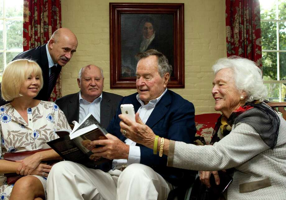 Former first lady Barbara Bush, far right, and former President George H.W. Bush sit with Mikhail Gorbachev, former leader of the Soviet Union, his daughter, Irina  Virganskaya and Pavel Palazhchenko before having lunch together Thursday, Nov. 1, 2012, in Houston. Mrs. Bush is looking at photos of Virganskaya's children on her iPhone. Photo: Brett Coomer, Houston Chronicle / © 2012 Houston Chronicle