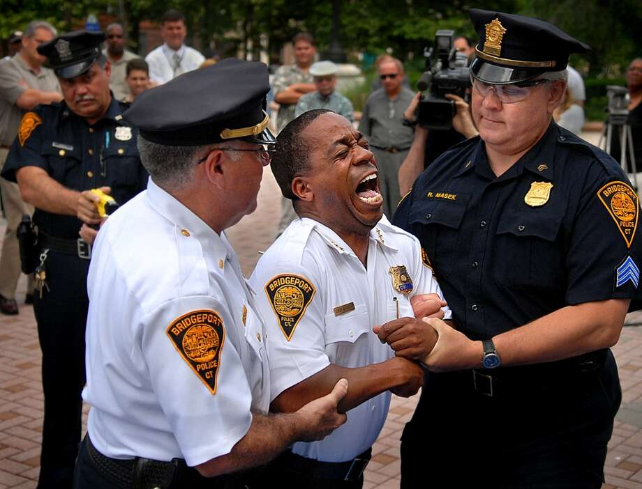 Former Bridgeport Police Chief Brian Norwood, center, reacts as he gets tasered  during a demonstration held outside the City Hall Annex, in Bridgeport, Conn. June 20, 2007. (Connecticut Post / File Photo)