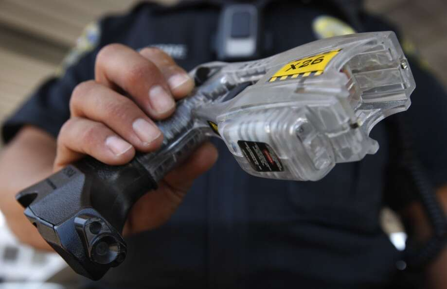 Police officer George Aguirre holds a Taser fitted with a video camera (lower left) in Brentwood, Ca