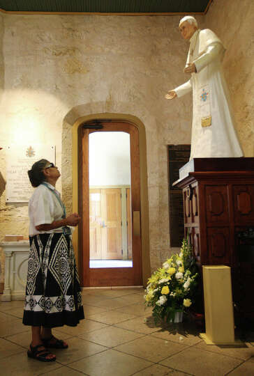 Catalina Hernandez, 64, prays by the statue of Pope John Paul, II at San Fernando Cathedral, Thur