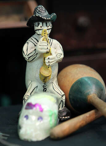 A statue depicting a spirit playing a saxophone is placed on an altar made by Roland Mazuca to honor his mother and father at the Rinconcito de Esperanza house on Tuesday, Oct. 30, 2012. About 20 altars were being put in the home which serves as a center for historical preservation for the Westside of San Antonio. A celebration for Dia de Los Muertos will be held at the home on Nov. 1 and will remain on display for 10 days thereafter. Photo: Kin Man Hui, San Antonio Express-News / ©2012 San Antonio Express-News