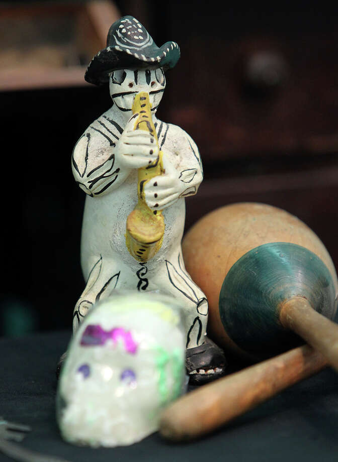 A statue depicting a spirit playing a saxophone is placed on an altar made by Roland Mazuca to honor his mother and father at the Rinconcito de Esperanza house on Tuesday, Oct. 30, 2012. Photo: Kin Man Hui, San Antonio Express-News / ©2012 San Antonio Express-News