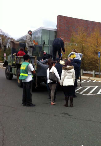 Fairfield University students board a Connecticut Air National Guard truck to tour their homes in the evacuated shoreline neighborhoods of Fairfield on Thursday. Photo: Linda Connor Lambeck / Connecticut Post