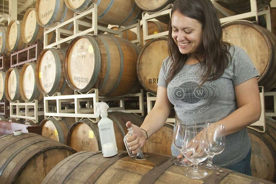 Alexandra Nowell, lead brewer at Drake's Brewing Co., siphons beer from a used bourbon barrel. Photo: Kelsey Williams, Drake's Brewing Co.