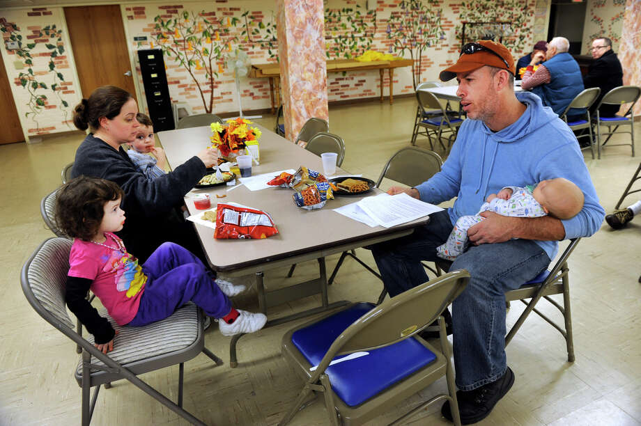 Ceri and David Burke, of Bethel,and their children, from left, Mikayla, 3, Patrick, 20 months, and Noah, five and a half weeks, at the emergency shelter at the Hurgin Municipal Center in Bethel, Ct. Thursday, Nov. 1, 2012. Their home is without power as a result of Hurricane Sandy. Photo: Carol Kaliff / The News-Times