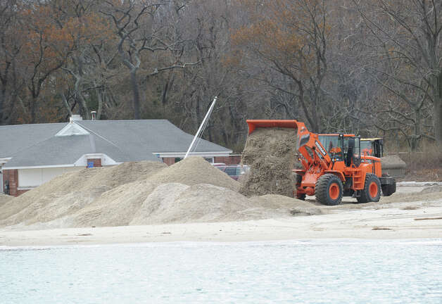 A loader dumps sand onto the beach at Greenwich Point as seen from Long Island Sound during a tour of the Greenwich coastline given by Greenwich Harbor Master Ian MacMillan of the damaged caused by Hurricane Sandy, November 1, 2012. Photo: Bob Luckey / Greenwich Time