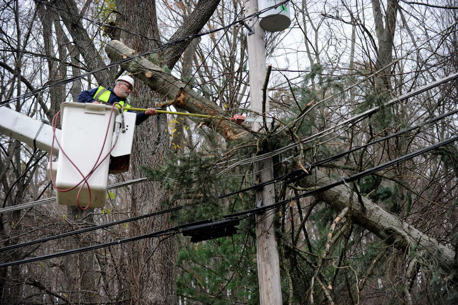 A worker from the Lewis Tree Service cuts down a tree branch that fell onto power lines on Joe's Hill Road in Danbury, Thursday, Nov. 1, 2012, during Hurricane Sandy. Photo: Carol Kaliff / The News-Times