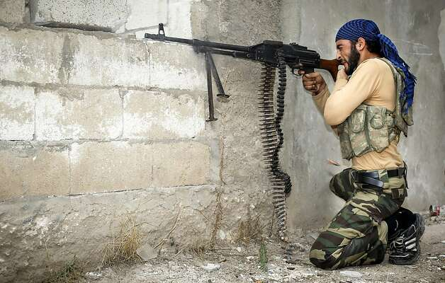 A rebel fires at Syrian troops in the citadel town of Harem on the Turkish border Wednesday. Rebels killed 78 soldiers Thursday, about half of them in attacks on military checkpoints. Photo: John Cantlie, AFP/Getty Images