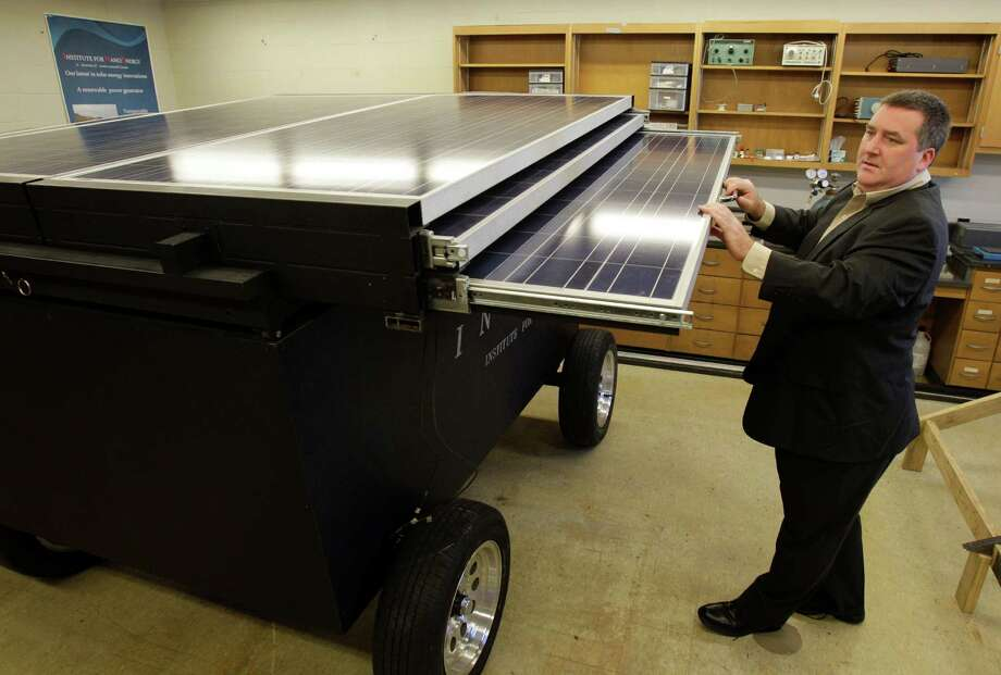 Seamus Curran, director of the Institute for NanoEnergy at the University of Houston, extends the solar panels on a unit called a Storm Cell. The panels can extend to 24 feet across and are 6½ feet wide and produce 2 kilowatts. Photo: Melissa Phillip, Staff / Houston Chronicle