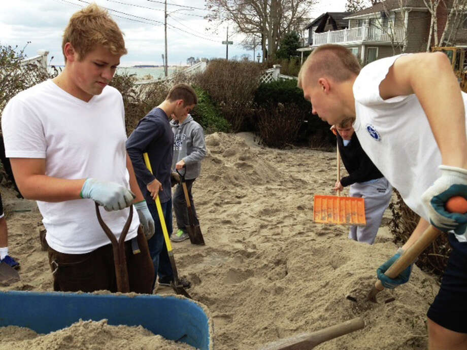 Staples soccer players Andreas Refvik (left) and Andrew Puchala remove some of the massive amount of sand from the front lawn of teammate Sebastian Hood Wednesday. Photo: Contributed Photo