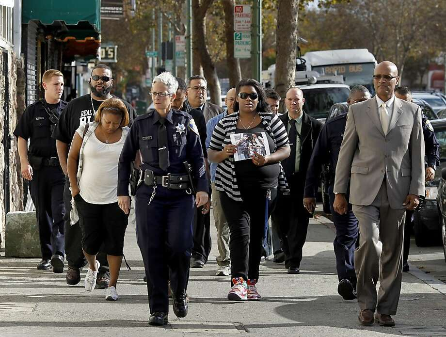 "Oakland Police Chief Howard Jordan (right), other police officials and members of Wilbur ""Will"" Bartley's family walk up East Oakland's International Boulevard on their way to the press briefing. A $15,000 reward has been offered for tips leading to an arrest in Bartley's slaying. Photo: Brant Ward, The Chronicle"