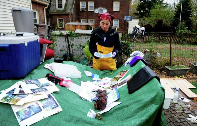 Lina Zapata looks at pages from her seventh-grade diary left out to dry at her mother's house in Seaside Village in Bridgeport, Conn. Thursday, Nov. 1, 2012.  Zapata, who was getting ready to leave the country for several months, was storing her belongings in her mother's basement and is now trying to salvage what she can following Hurricane Sandy which filled the basement with over 5 feet of water. Photo: Autumn Driscoll / Connecticut Post
