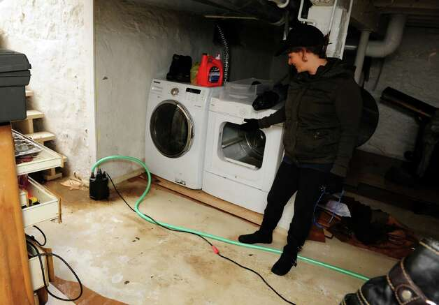 Luz Gutierrez points out the water in her dryer at her home in Seaside Village in Bridgeport, Conn. Thursday, Nov. 1, 2012.  It took several attempts to pump water left behind from Hurricane Sandy from the basement since it kept seeping back in from the ground and other homes. Photo: Autumn Driscoll / Connecticut Post