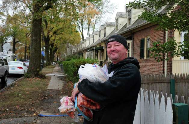 Tibor Kiss carries meat from a neighbor's freezer back to his house at Seaside Village in Bridgeport, Conn. Thursday, Nov. 1, 2012.  Kiss was one of the lucky few in Seaside Village with power. Photo: Autumn Driscoll / Connecticut Post