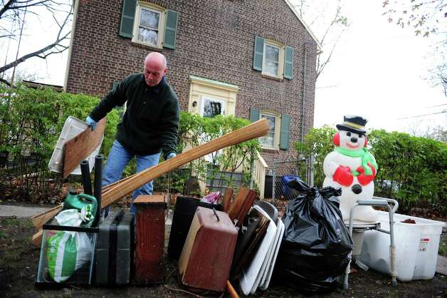 John Quintiliano carries items to the curb outside his home in Seaside Village in Bridgeport, Conn. Thursday, Nov. 1, 2012.  Most belongings in his basement, which flooded during Hurricane Sandy, were not salvageable. Photo: Autumn Driscoll / Connecticut Post