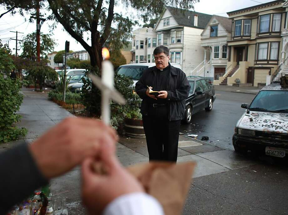 Father Michael Quinn (right) of St. Brendan's Church reads to those gathered during a prayer service for Cesar Bermudez on Harrison Street where Bermudez was killed on October 24, 2012 on Thursday, November 1, 2012 in San Francisco, Calif. Photo: Lea Suzuki, The Chronicle