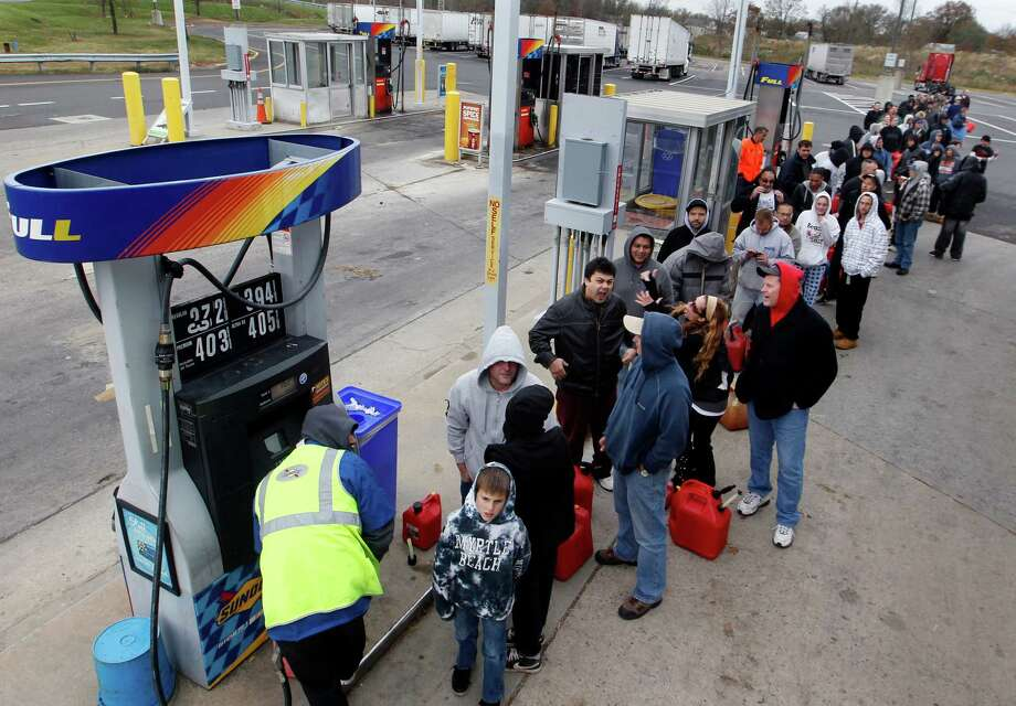 People line up to fill gas containers at the New Jersey Turnpike's Thomas A. Edison service area Wednesday, Oct. 31, 2012, near Woodbridge, N.J. The price of oil is rising as operations at refineries and supply terminals in the Northeast remain restricted three days after Superstorm Sandy. Benchmark oil gained 60 cents Thursday to $86.84 per barrel in New York.  (AP Photo/Mel Evans) Photo: Mel Evans, STF / AP