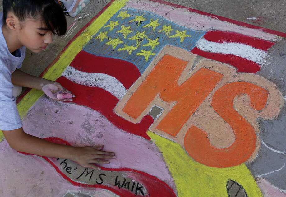 Leslie Fraire fills in her team's sketch as they participate in the Chalk the Walk for MS at Marshall Academy of Fine Arts on Thursday, Nov. 1, 2012, in Houston. Approximately 66 local students participated in The Chalk the Walk for MS competition. The designs serve as a powerful artistic symbol of the steps Houstonians will take at Walk MS: Houston Series 2012.  Thousands of walkers are challenging themselves and others to raise funds for MS research and programs. Photo: Mayra Beltran, Houston Chronicle / © 2012 Houston Chronicle