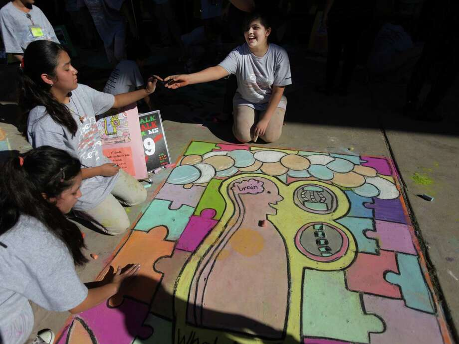 Yuliza Lara, 13, Angelina Sosa, 12, and Abigail Garcia, 12, smile as their design is nearly complete while participating in The Chalk the Walk for MS competition at Marshall Academy of Fine Arts on Thursday, Nov. 1, 2012, in Houston. Photo: Mayra Beltran, Houston Chronicle / © 2012 Houston Chronicle