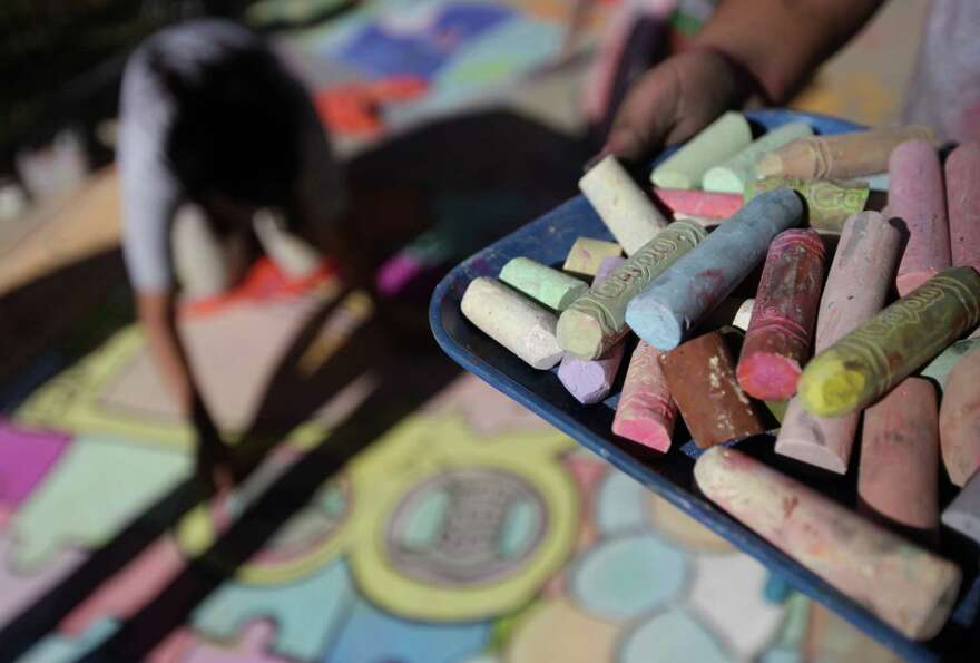 A student collects chalk as approximately 66 local students are nearly done with their chalk art ent