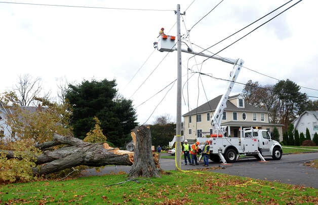 Power company crews from Thirau, which is contracted by United Illuminating, work to repair power lines after damage from Hurricane Sandy on Ridgewood Drive in Milford, Conn. on Thursday November 1, 2012. Photo: Christian Abraham / Connecticut Post