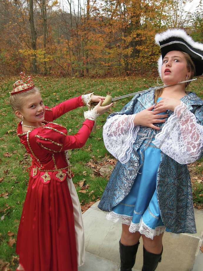 "Alyssa and Kayla of Clifton Park dress up for Halloween in costume custom made by their grandmother and have fun as ""The Queen"" and a musketeer."