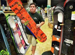 Alpin Haus' Ski department manager James Georgelos stacks snow boards for this year's Albany Ski and Snowboard Expo in Convention Center at the Empire State Plaza in Albany Thursday Nov. 1, 2012.  (John Carl D'Annibale / Times Union)