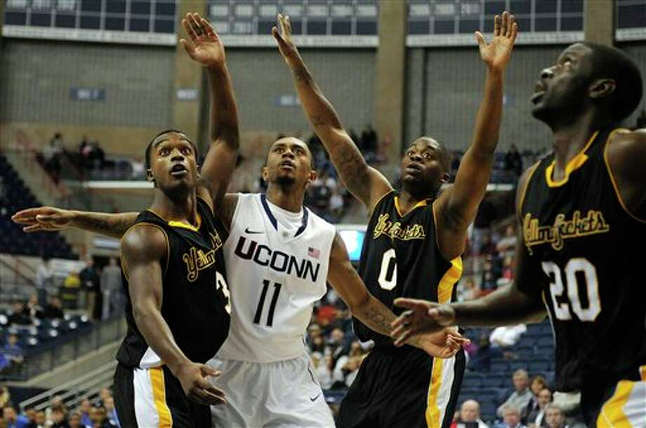 Connecticut's Ryan Boatright (11) and American International College defenders  Spencer Braithwaite (3), Jason Perrier (0), and Sesoo Ikpah (20) watch  Boatright's shot during the first half of a men's NCAA basketball game  in Storrs, Conn., Thursday, Nov. 1, 2012. (AP Photo/Jessica Hill)