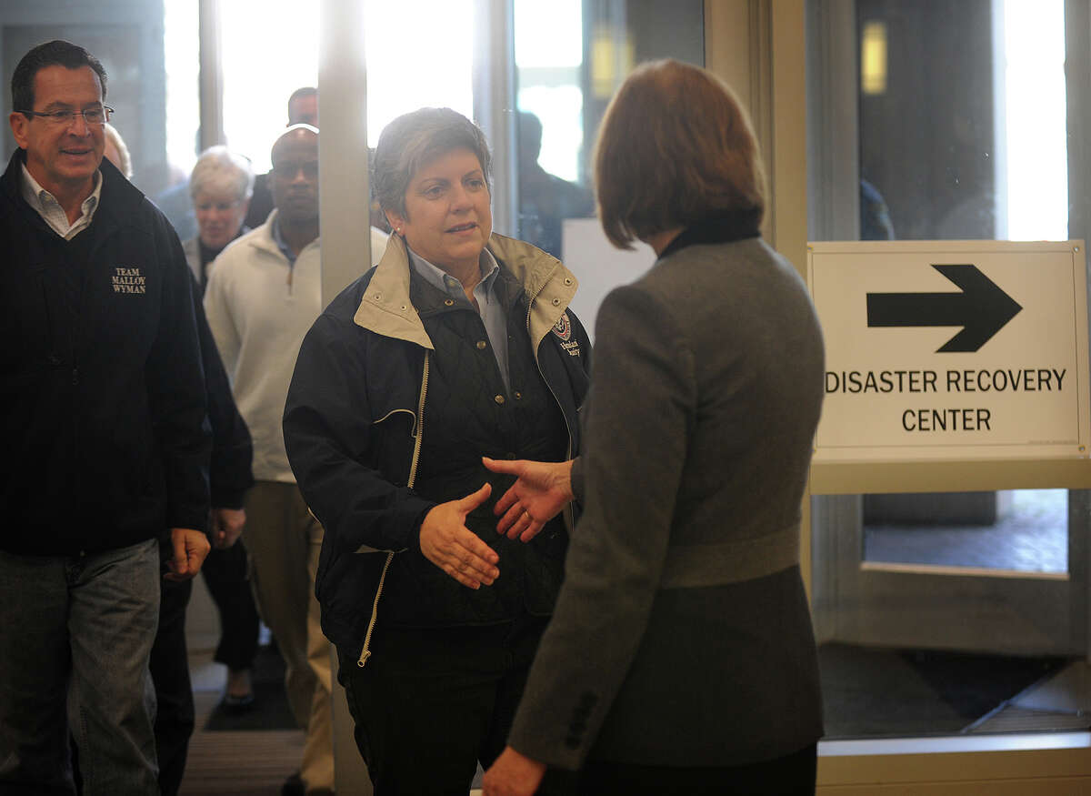Flanked by Gov. Dannel Malloy, left, Homeland Security Secretary Janet Napolitano is greeted by Housatonic Community College President Anita Gliniecki as she arrives to meet with local and state officials in Bridgeport on Thursday, November 1, 2012.