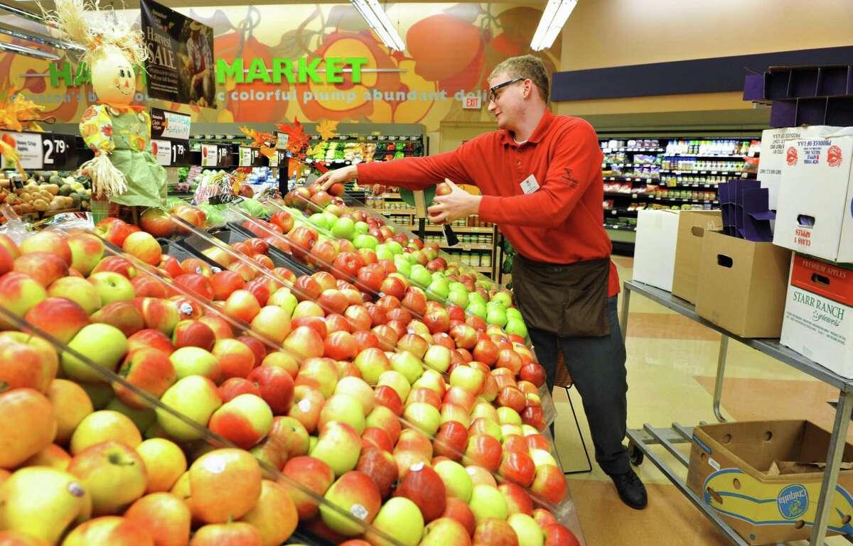 Assistant produce manager Matt Schmit stocks apples at the Hannaford supermarket on Columbia Turnpike in East Greenbush Thursday Nov. 1, 2012. (John Carl D'Annibale / Times Union)