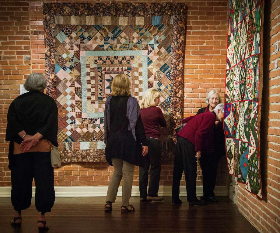 Lenore Millspaugh, right, pears behind an embroidered quilt from 1900 as Patti Haney, second from left, and other visitors from Pearl Fincher Museum of Fine Arts look at the selection of quilts at the Texas Quilt Museum, Friday, Oct. 26, 2012, in La Grange. Photo: Michael Paulsen, Houston Chronicle / © 2012 Houston Chronicle
